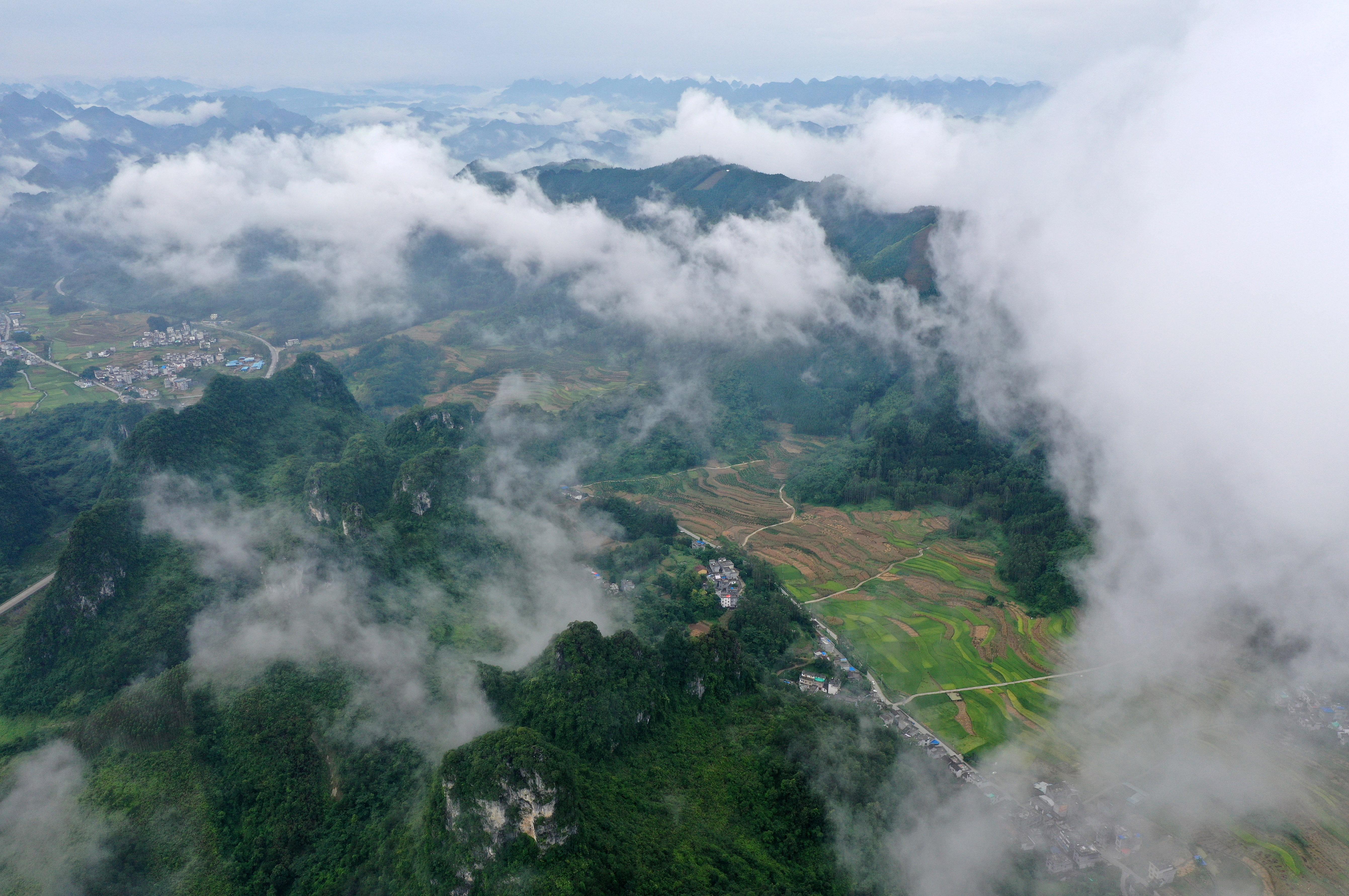这是7月24日无人机拍摄的广西都安瑶族自治县下坳镇云雾缭绕的风景。     当日,在广西都安瑶族自治县下坳镇,云雾缭绕于群山大地之间,充满诗情画意。     新华社记者 陆波岸 摄