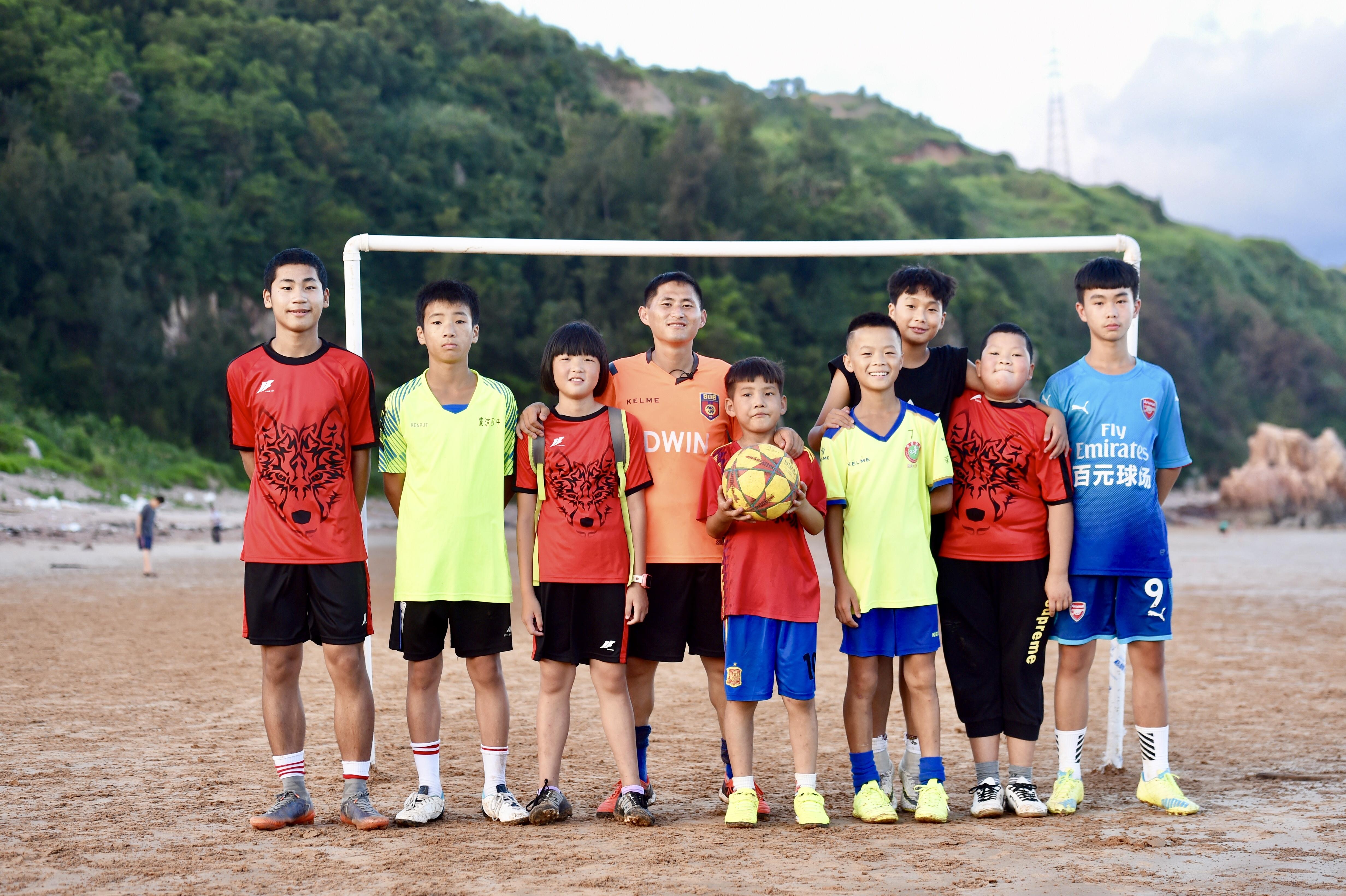 """阳光,海浪,足球,孩子们的笑声。     在福建霞浦,有一个""""百元球场"""",一位""""另类""""教练。     他的背后,是一群面朝大海、迎风踢球的孩子。     他们的背后,足球与海的故事已延续上百年。     图为7月17日,福建省霞浦县下浒镇外浒沙滩上,""""长风""""足球队教练陈龙强(左四)与小球员们在水管搭建的简易球门前合影。     新华社记者 姜克红 摄"""
