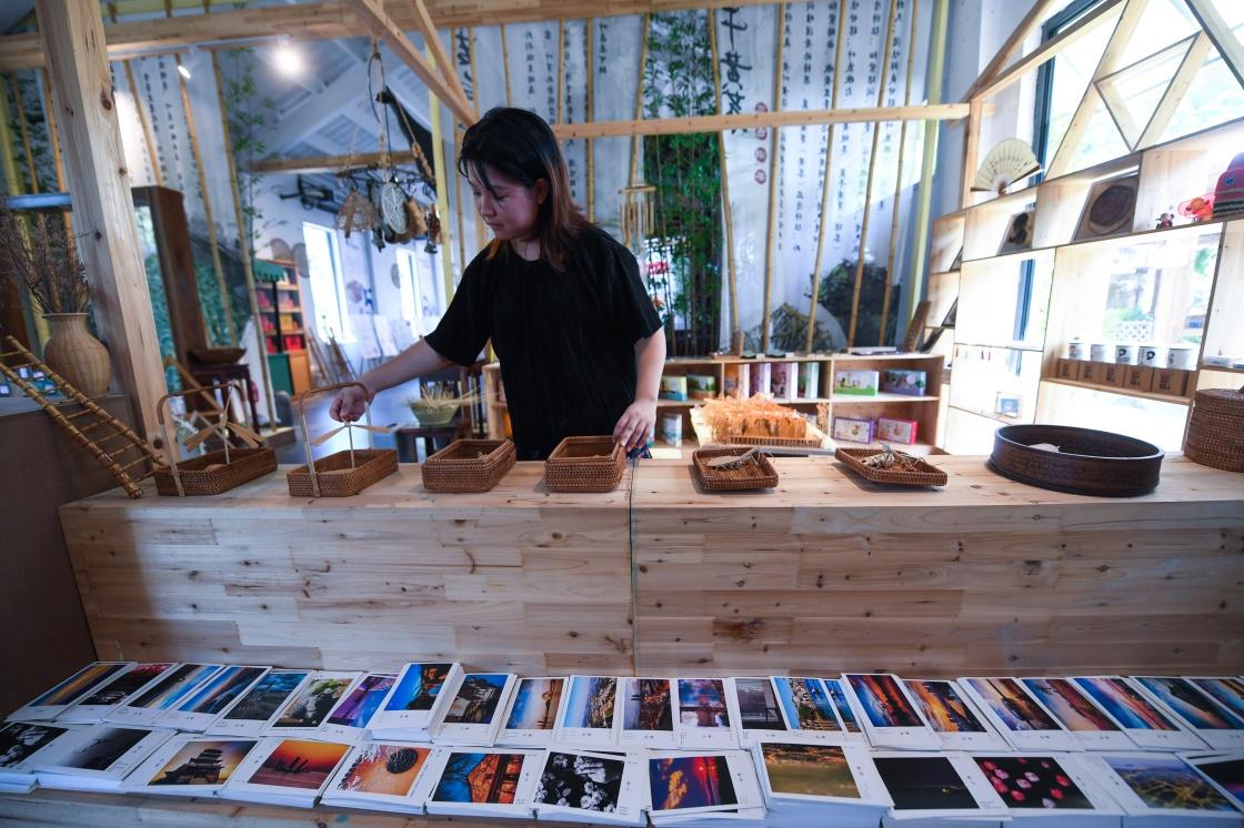 8月7日,在妙西镇一家乡村小型文化综合体内,工作人员展示特色手工旅游产品。新华社记者 徐昱 摄
