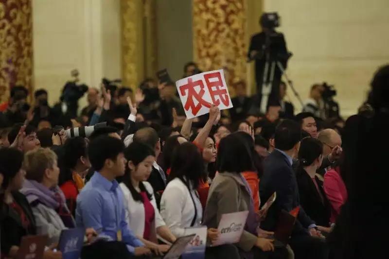 """亚游国际游戏官网记者江娜举着""""农民""""字牌争取提问机会"""