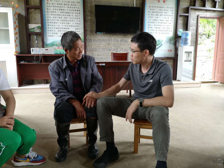 【滇桂黔石漠化区】农民日报记者李飞在云南省西畴县岩头村采访,与修路带头人李华明手拉手话家常。